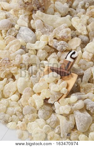 Frankincense in a wooden spoon. Frankincense is an aromatic resin, used for religious rites, incense and perfumes