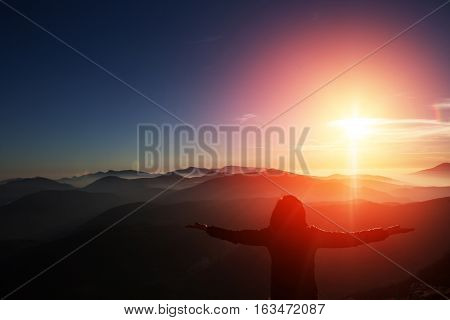 Woman on top of mountain celebrating succes. Trip concept.