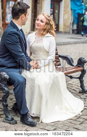 newly-weds sit on the bench in the city