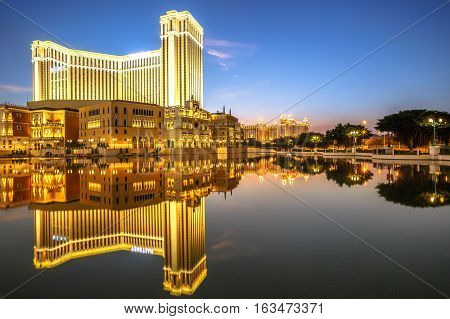 Macau, China - December 8, 2016: golden light illumination of The Venetian Macau mirroring on lake at twilight, the largest casino in the world and the largest single structure hotel building in Asia.