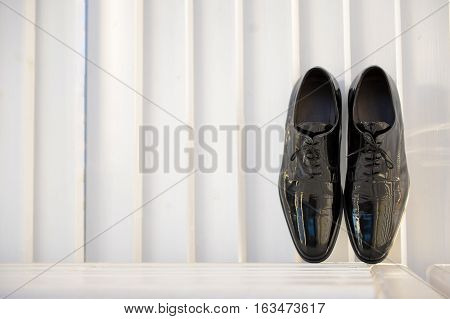 Groom shoe at home in natural light
