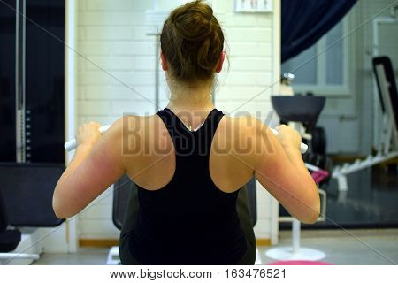 Woman working out her back muscles and arms with pulley at the gym.