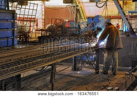 Tyumen, Russia - August 13, 2013: Block making department at construction material factory ZHBI-5. Welder with protective mask welding metal and sparks
