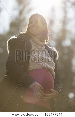 High key image with sun flare of a smiling pregnant woman standing outdoors in the garden clasping her belly from below with her hands in a wellness and childbirth concept.