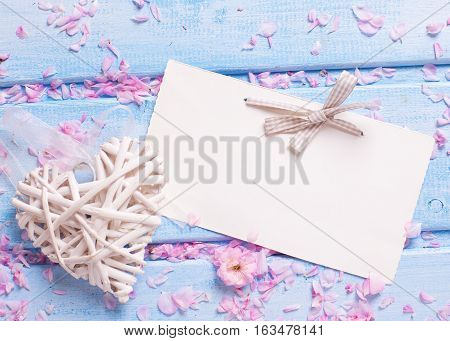 Background with decorative heart petals sakura flowers and empty tag on blue wooden planks. Selective focus. Place for text.