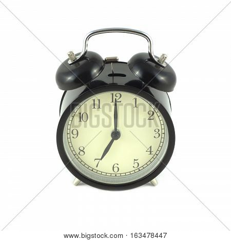 Alarm clock in black case shows 7 o'clock. Front view isolated on white closeup