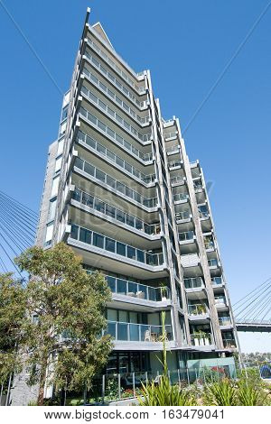 Multilevel Sydney apartment with Bright Blue Sky and tree garden in the foreground. Pyrmont Sydney New South Wales Australia.