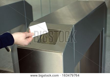 Woman's hand puts white plastic card indoor to electronic reader security access control system. Closeup view