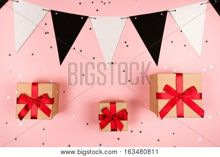 Present with red bow and decorative festive flags on pink background with tittle sparkles. Flat lay style.