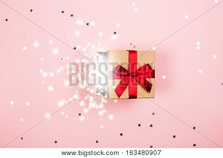 Opened present box with red bow and magic inside on pink background with tittle sparkles. Flat lay style.