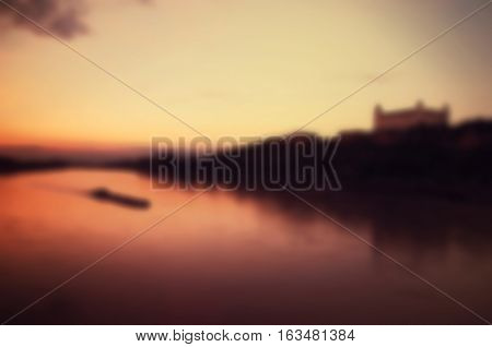 Blurred vintage background of sunset on the Danube River with Bratislava Castle View in Bratislava, Slovakia