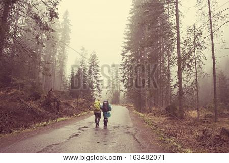 Two hikers on a path throught the forest in the mountains. Vintage hipster red colors