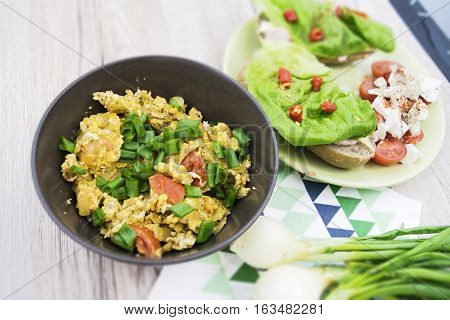 Scrambled eggs in the brown bowl. Sandwiches with lettuce and hot peppers. Wooden background. Top view