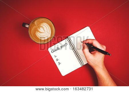 Man's hands on the table are writing New Year goals in note book. Near is cup of aromatic coffee for inspiration. Planning day.