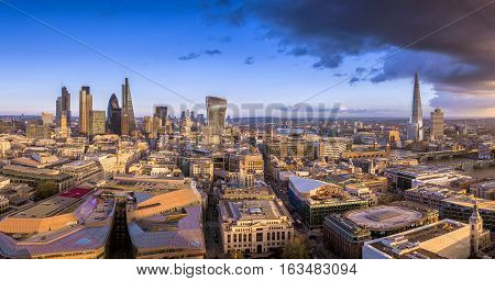 London England - Panoramic skyline of the famous bank district of London the leading financial district of the world at sunset with skyscrapers and dark clouds