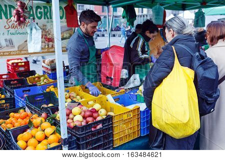 Naples Italy - January 11 2016: Piazza Dante fruit counter market. A lady at the counter of the fruit interacts with the clerk before making purchases. Featured overflowing boxes of fruit apples oranges tangerines etc.
