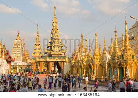 YANGON MYANMAR - NOVEMBER 26 2016: people and monks at the sunset in the Shwedagon pagoda. The Shwedagon pagoda is the most famous pagoda of south est Asia