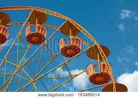 Colorful ferris wheel detail over blue sky