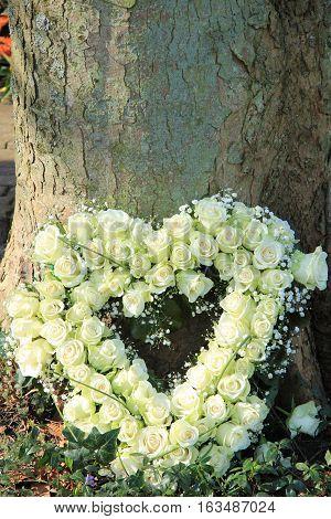 Heart shaped sympathy flowers near a tree