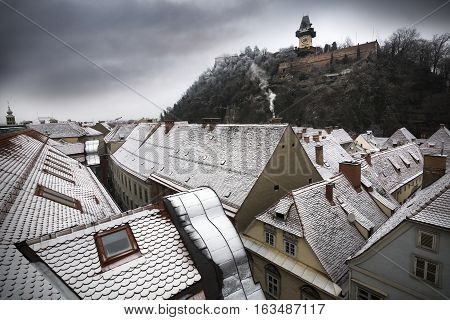 Snowy rooftops in Austrian city of Graz with landmark clocktower