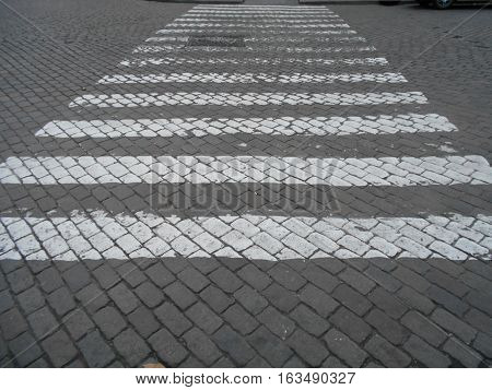 Crosswalk zebra in a white road through the cobbled roadway
