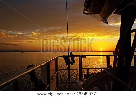 Golden Sunset seascape from a boat with water reflections. At sea Queensland Australia.