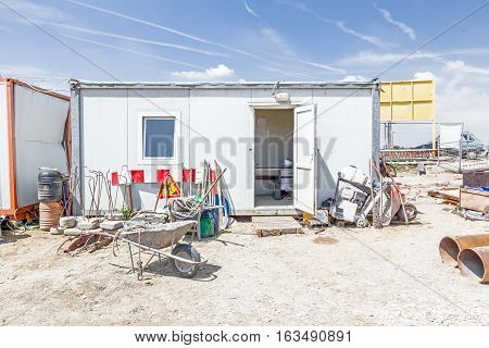 Makeshift storage material and tools for ground work in front of container office at building site.