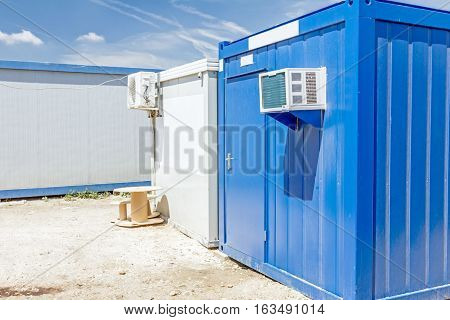 Outdoor unit compressor of air conditioner is placed on container office.