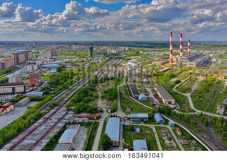 Aerial view of modern combined heat and power plant. Fuming chimney with sulphur removal unit. Heavy industry from above. Power and fuel generation in Tyumen. Russia