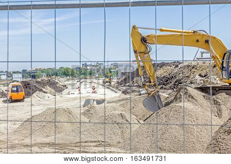 Yellow excavator is making pile of gravel by pulling ground up on heap at construction site project in progress.