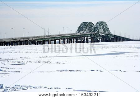 The great south bay is frozen unerneath the robert mosses bridges off of Long Island