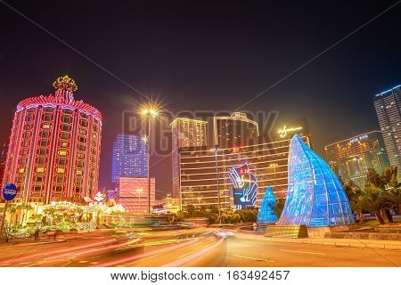 Macau, China - December 8, 2016: Cityscape of the Macao business district with popular casinos: Wynn Macau, MGM Macau and Casino Lisboa. Macao street illuminated at night.