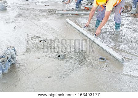 Mason is using a trowel to finish top of the concrete foundation.