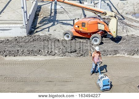 Above view on worker who is working with vibration plate compactor machine.
