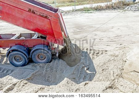 Red dumper truck is unloading sand at construction site.