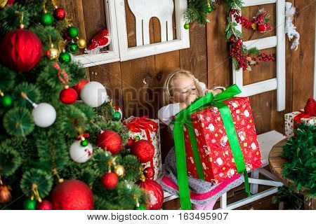 Beautiful happy girl unwrap christmas present box on holiday morning in beautiful room interior. Female child open Xmas gift near decorated fir tree. Winter holidays concept