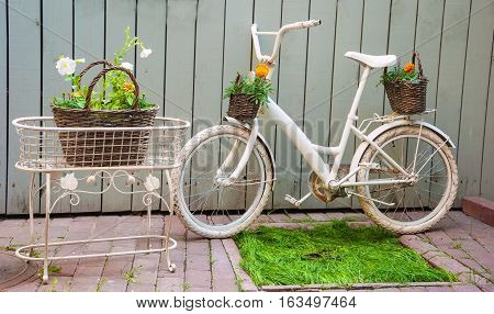 Gardening composition with a bicycle and a basket of flowers