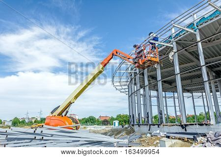 High elevated cherry picker people are working at new assembled canopies on construction site.