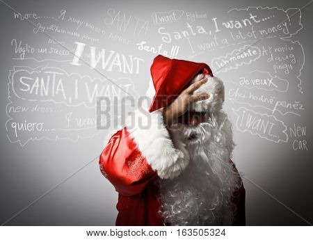 Frustrated Santa Claus. Santa Claus suffering from headache and many wishes.