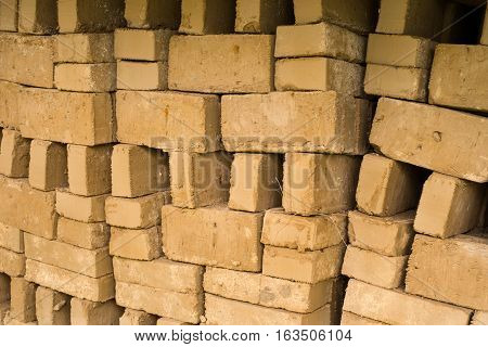 Stack of raw bricks drying in the open air.