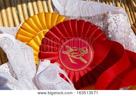 Award rosettes for winner in equestrian sport with red and yellow colours