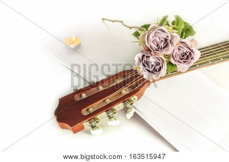A photo of a guitar neck with tender pink roses and blurred sheet music, on a white background with copyspace