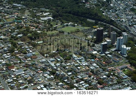 Aerial of Pali Highway winding through Nu'uanu Valley Neighborhood with homes Condos and Graveyards on Oahu Hawaii.
