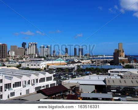 Aerial view of the Honolulu Port and downtown skyline with landmarks Aloha Tower Nimitz Highway and modern skyscrapers on Oahu Hawaii. July 2016.