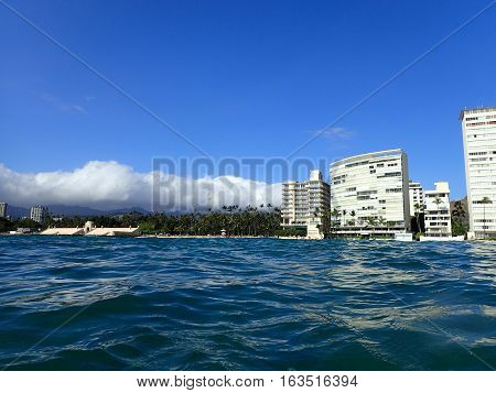 Wavy water on ocean off Kaimana Beach with hotels and condos on Oahu Hawaii.