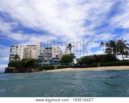 Makalei Beach with waves lapping napakaa lava rock wall and Coconut trees with Condos in the background along the shore on a wonderful day in Oahu Hawaii.
