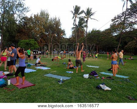 HONOLULU HI - MAY 15 2016: Group of people practice AcroYoga handstands and hula-hooping in Kapiolani Park at dusk on Oahu Hawaii May 15 2016.
