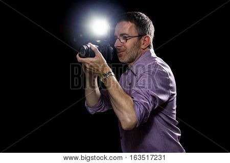 Paparazzi Photographer working at night with a camera and flash