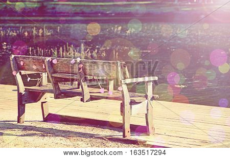 Dreamy summer day with decorated wooden park bench by the river. Retro toned image with sun flare and bokeh lights. Relaxing summer lifestyle and leisure concepts.
