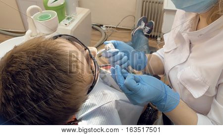 Woman at the dentist clinic office gets dental medical examination and treatment. Odontic and mouth health is important part of modern human life that dentistry help with.